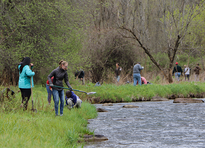 Students in foreground adults in background along river