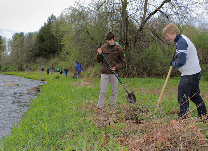 Two students digging along river volunteers in background